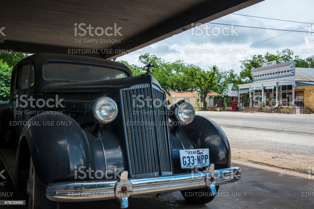 An old car with the general store and post office on the background...