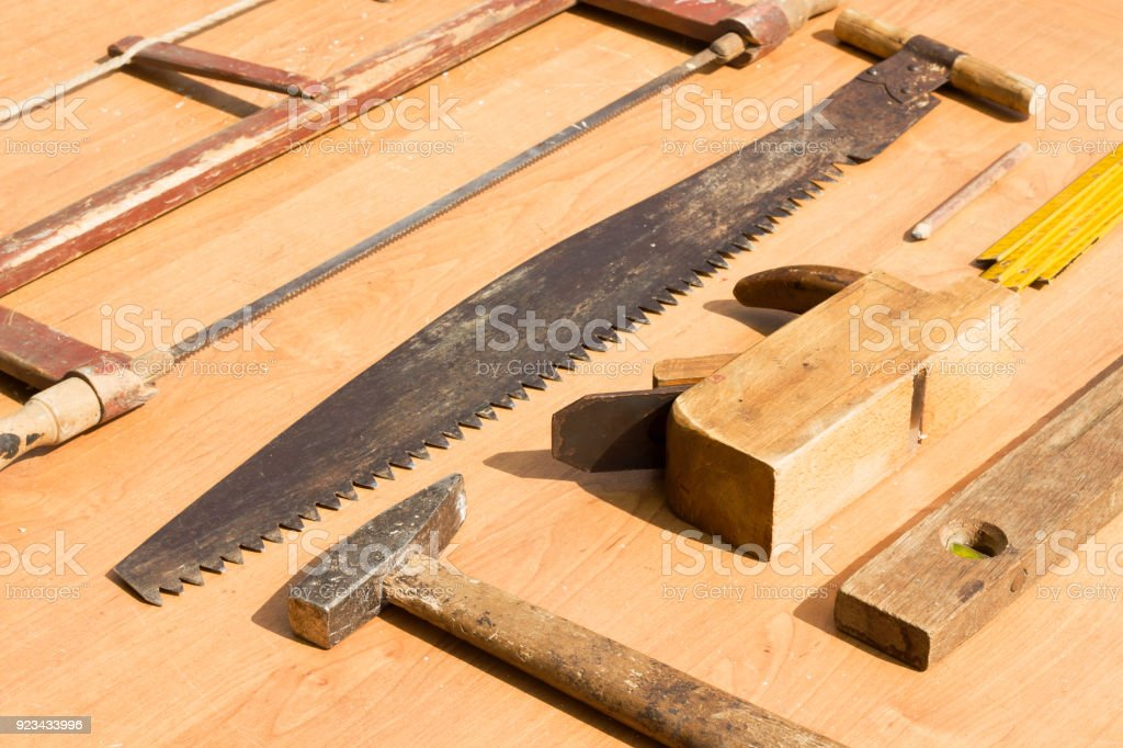Old carpenter tools lie on the table. plane, saw, level, scoop, hammer, pencil, stock photo