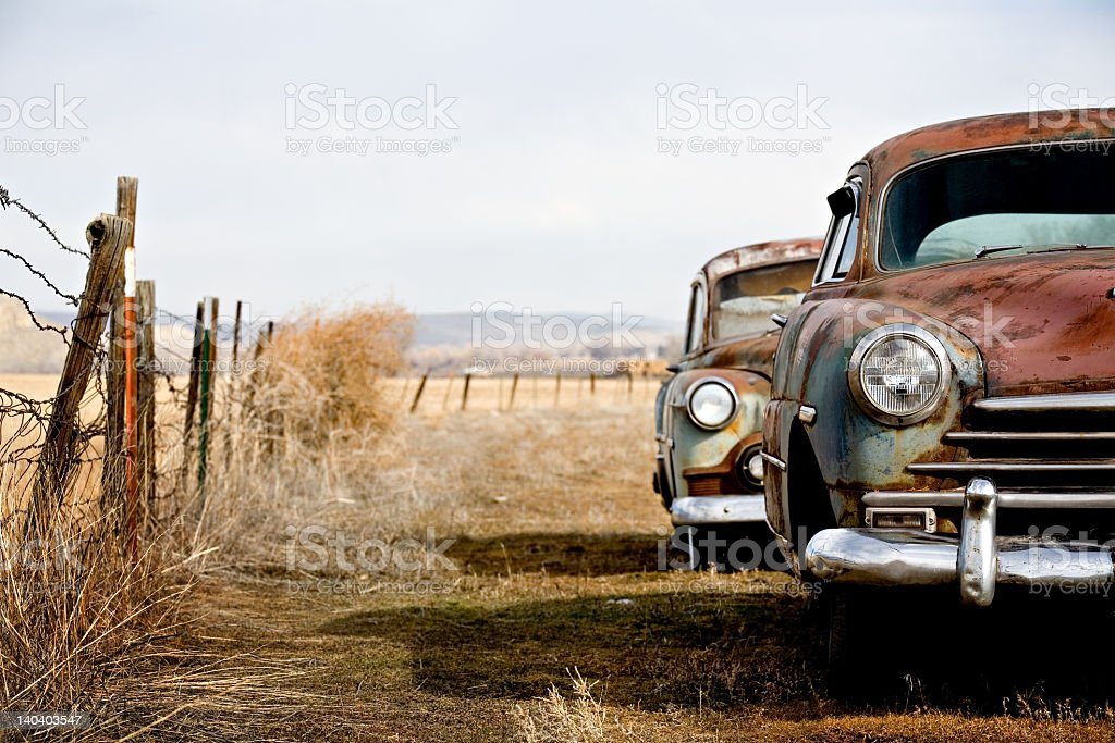Old cars abandoned in a fenced field stock photo