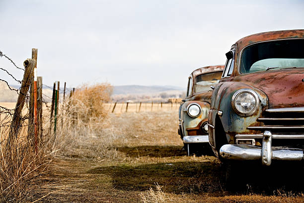 old cars abandoned in a fenced field - 過時的 舊式 個照片及圖片檔