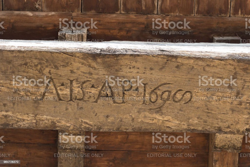 Old carved lettering on a wooden board on the Arnolfo Tower rooftop of Palazzo Vecchio, Florence, Tuscany, Italy. royalty-free stock photo
