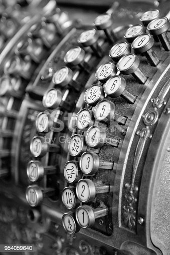 Details of keys of an old mechanical metal calculator . Black and white.