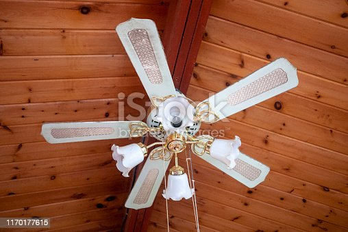 Dirty old ceiling fan hanging below a wood-panelled a-frame ceiling in a cottage.