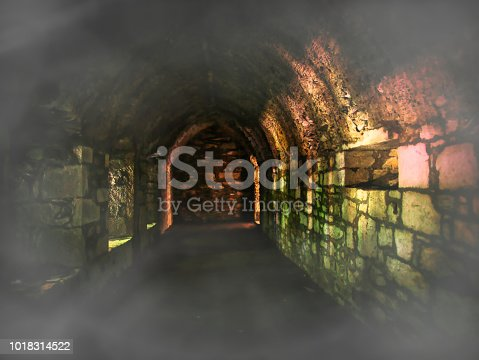 Underground tunnel or cellar with fog and colorful light effects on the individual stones from the brickwork