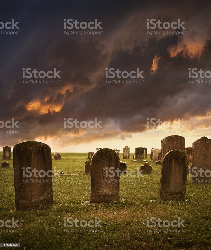 Old cemetery tombstones with spooky clouds stock photo