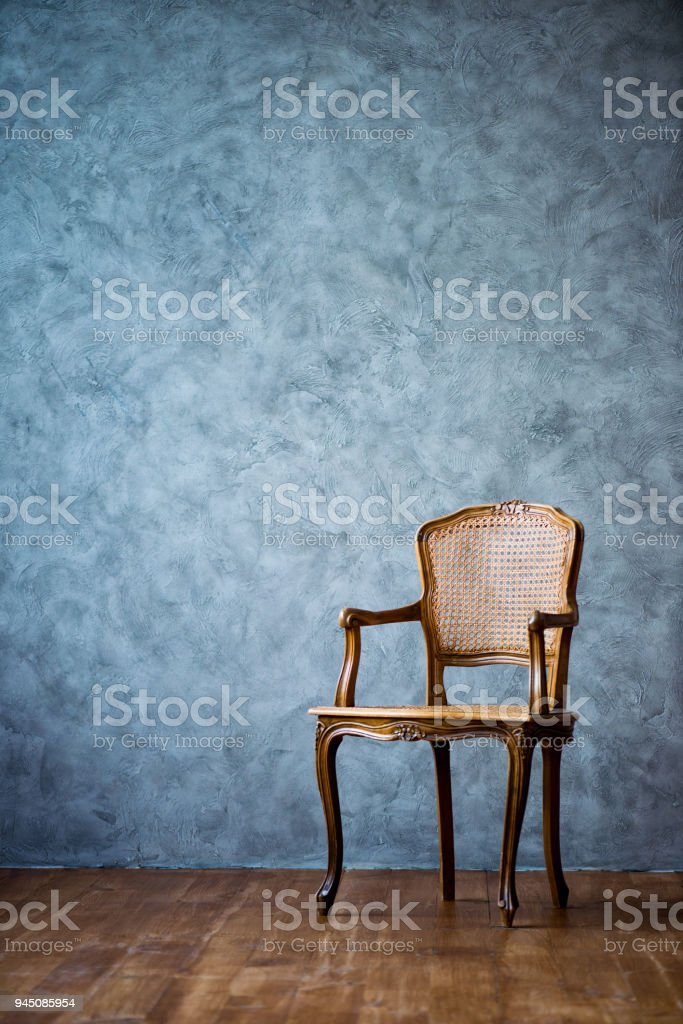 old chair on a gray wall background стоковое фото
