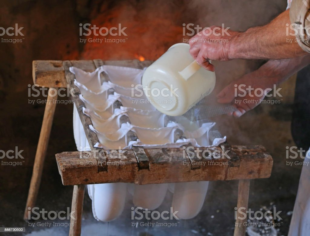 old cheesemaker during the preparation of the cheese in the chee stock photo