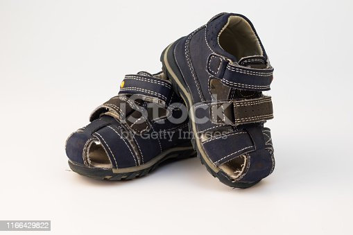 istock Old children's sandals in blue on a white background. 1166429822