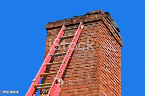 Red ladder against old chimney to make needed repairs