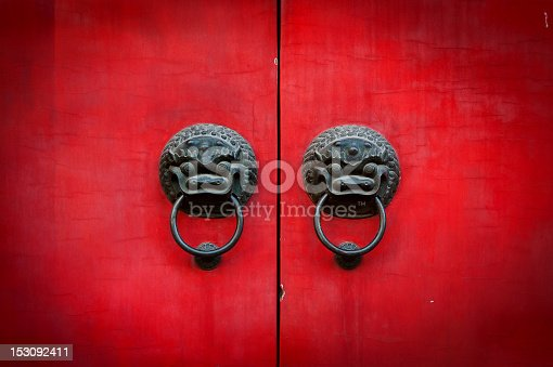 Old chinese red door with lion head metal knockers