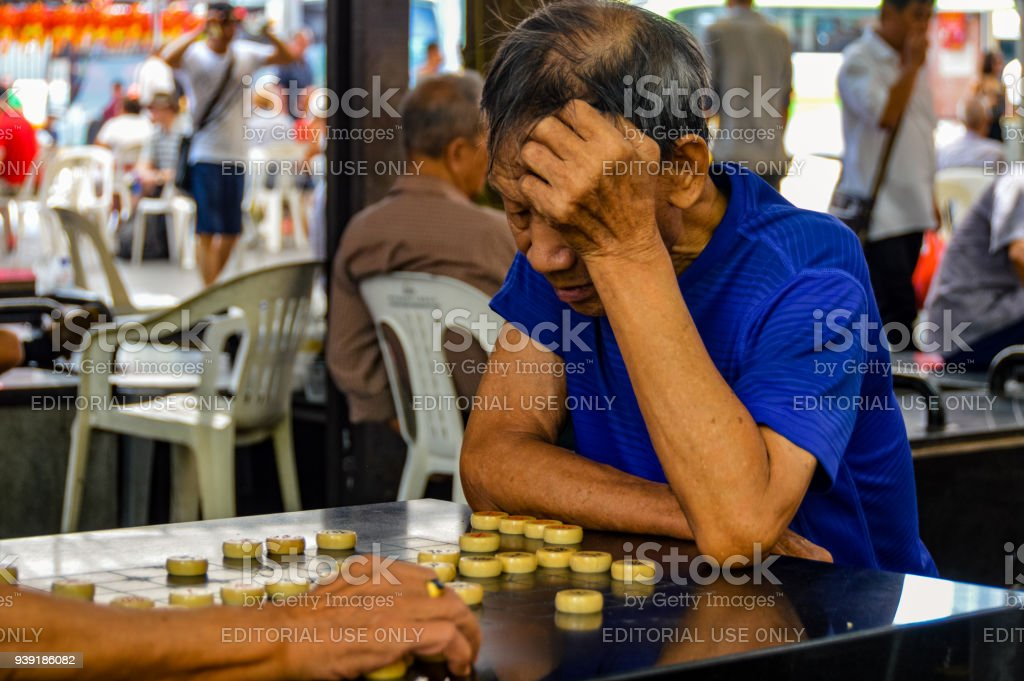 Old Chinese man playing games in Chinatown stock photo