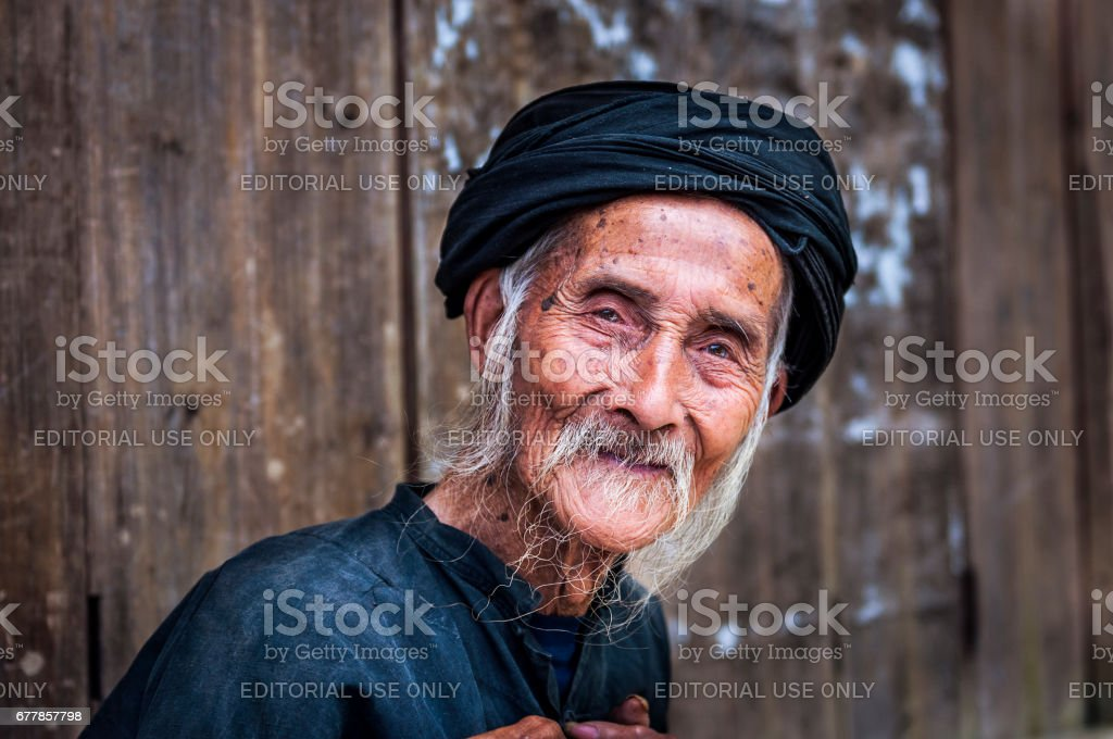 Old Chinese man wearing traditional clothes in Dazhai, Guangxi, China stock photo