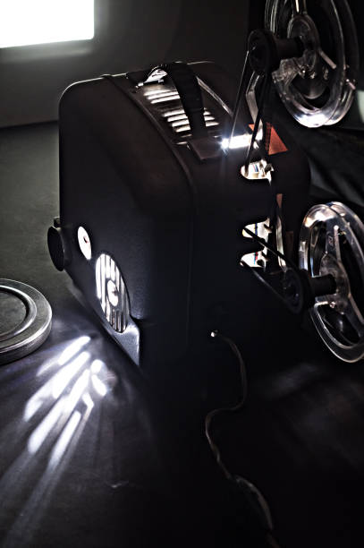 Old cinema projector and a glowing screen in the dark stock photo