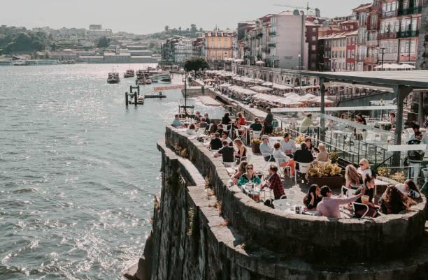 old city houses over douro river and many tourists having lunch at outdoor restaurant - esplanada portugal imagens e fotografias de stock