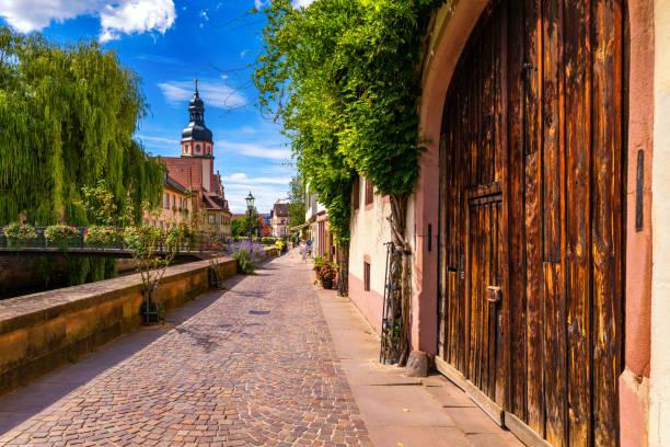 Altstadt von Ettlingen in Deutschland mit einem Fluss und einer Kirche. Blick auf einen zentralen Ortsteil von Ettlingen, Deutschland, mit einem Fluss und einem Glockenturm einer Kirche. Ettlingen, Baden-Württemberg. – Foto
