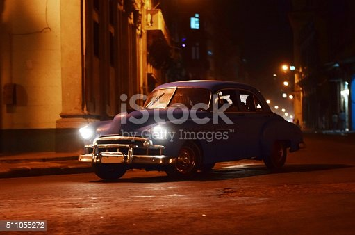 Front/left side shot on the old classic American car driving on the Havana street at night.