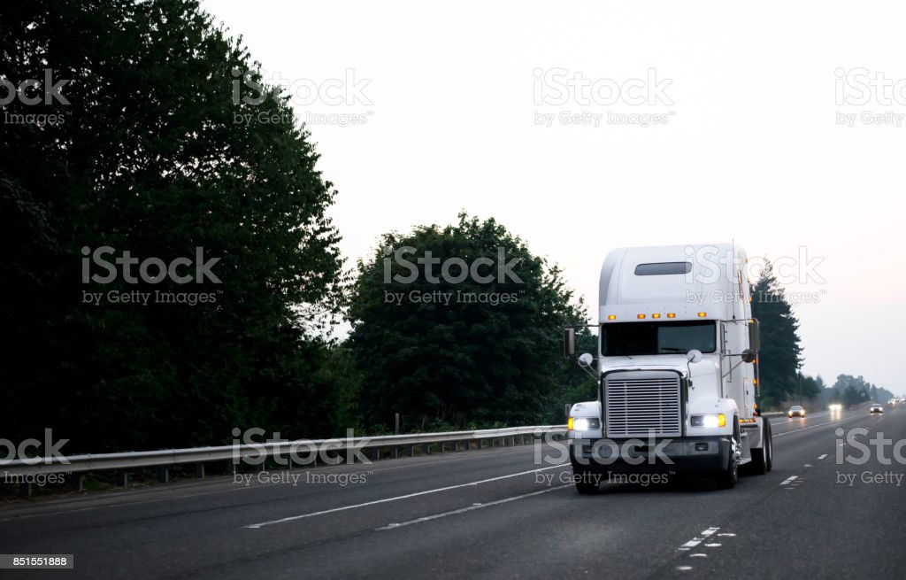 Old classic big rig power semi truck tractor driving by wide evening highway stock photo