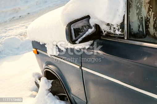 Old classic car covered in snow. Snow-covered car blocked after heavy snowstorm.