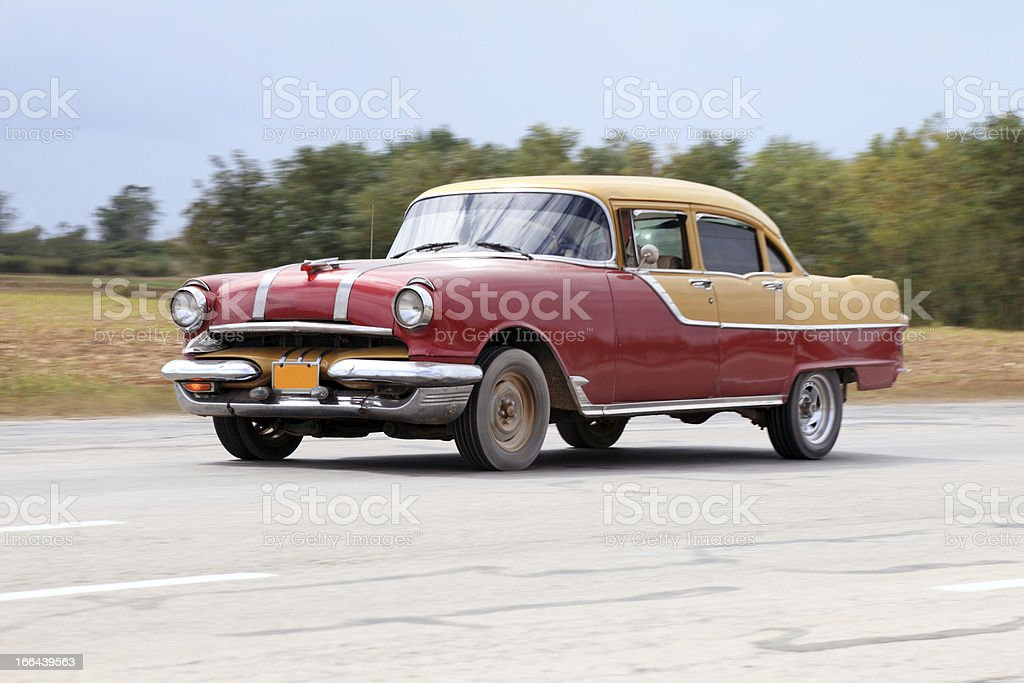 Old classic car drives by Cuban highway stock photo