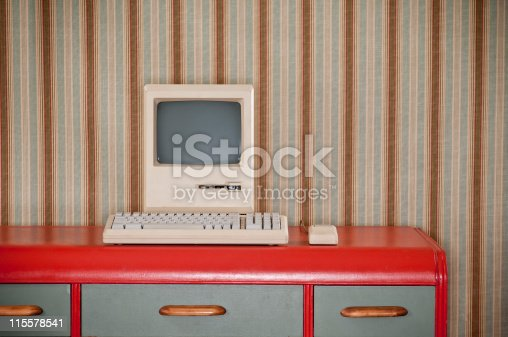 Old classic computer sitting on an art deco retro desk. The wall is covered in a wallpaper with a striped wallpaper.*