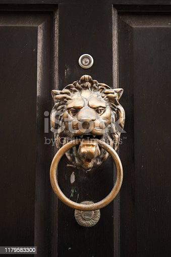 Old classic doorknob in shape of lion head with ring mounted on dark vintage wooden door, close-up photo