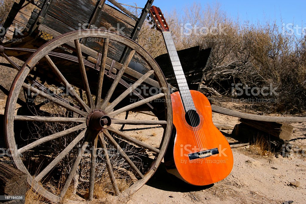Old Classical Guitar in Western Scene with Wagon Wheel stock photo