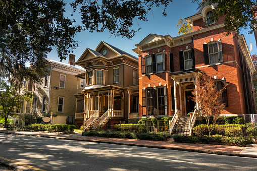 Tree lined historic homes on a residential street in Savannah Georgia USA