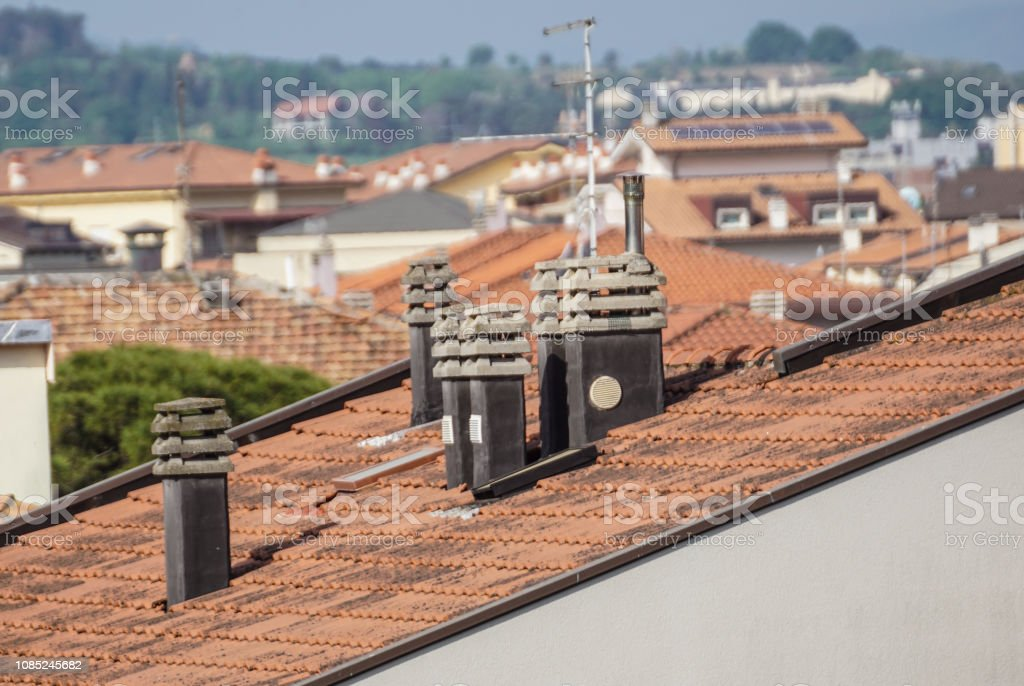 Old clay chimney pots and brick chimney stacks on old tiled roof complete with TV aerials in England, UK. - foto stock