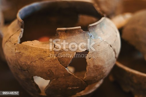 an old clay jug with large cracks stands on the shelf