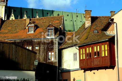 old clay sloped residential roof in downtown Zagreb. small wooden dormers. aged deep brown wood slat finished house exterior with yellow windows. old European architecture & travel concept
