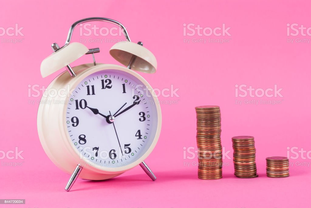 Old clock and coins on pink background stock photo