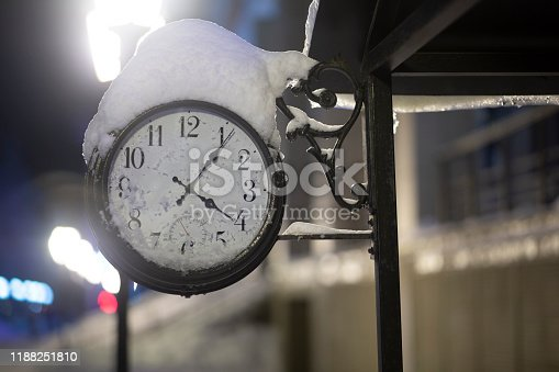 Old clock at night in winter on the street of the city.