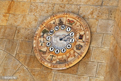 Old clock face shows time signs zodiac on western wall city Jerusalem.