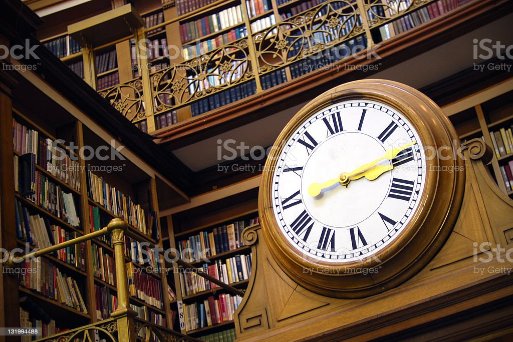Old clock in the library stock photo