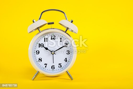 istock Old clock on yellow background and space for text 848765738