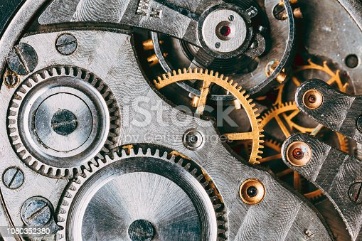 Close-Up Of Old Clock Watch Mechanism. Retro Clockwork Watch With Gray And Golden Gearwheels Gears. Vintage Movement Mechanics