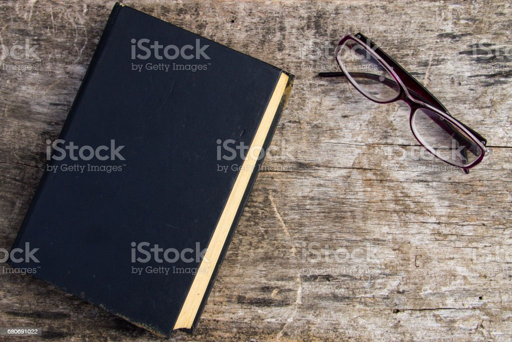 Old closed book and glasses on wooden background stock photo