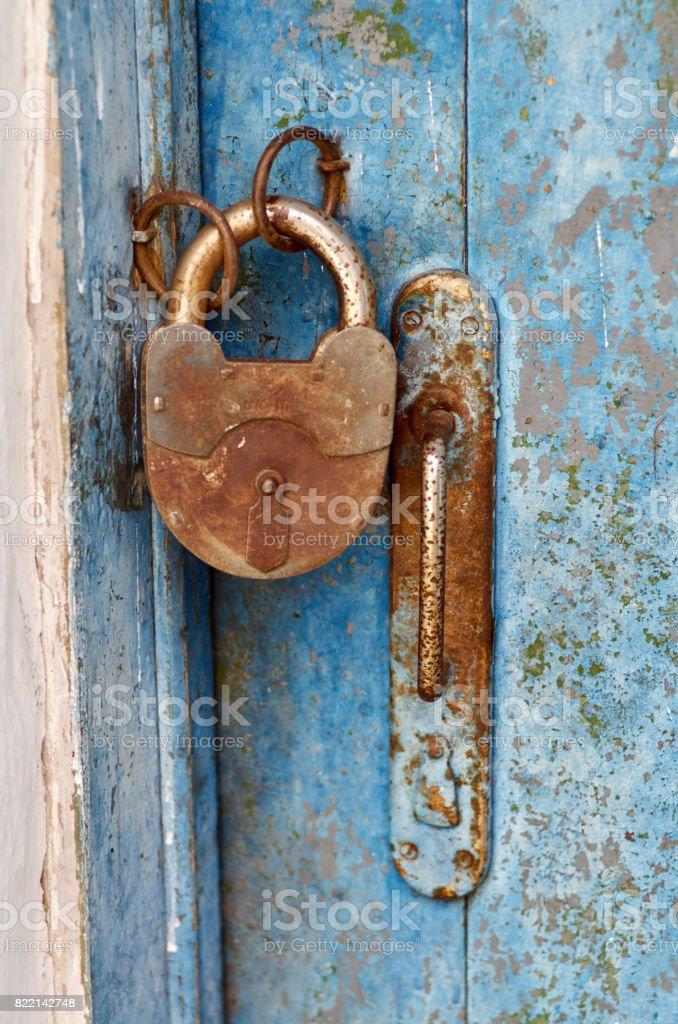 Old closed padlock rusty on wooden weathered door stock photo