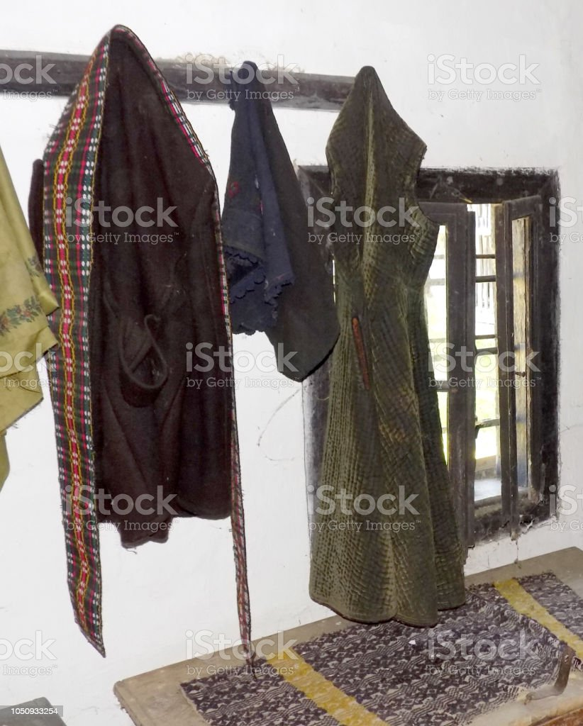 Old clothes hanging on the hat stand in the old room