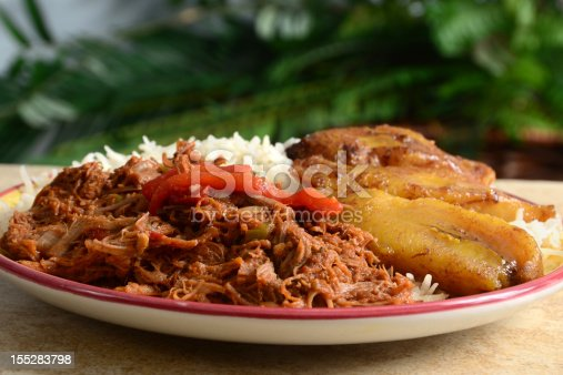 Ropa Vieja is a classic Cuban stew of shredded beef, served here with white rice and fried plantains.