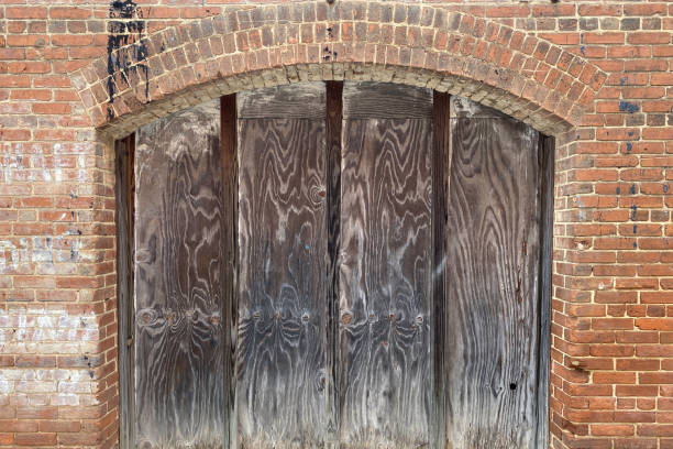 old coal chute door behind old red brick house stock photo