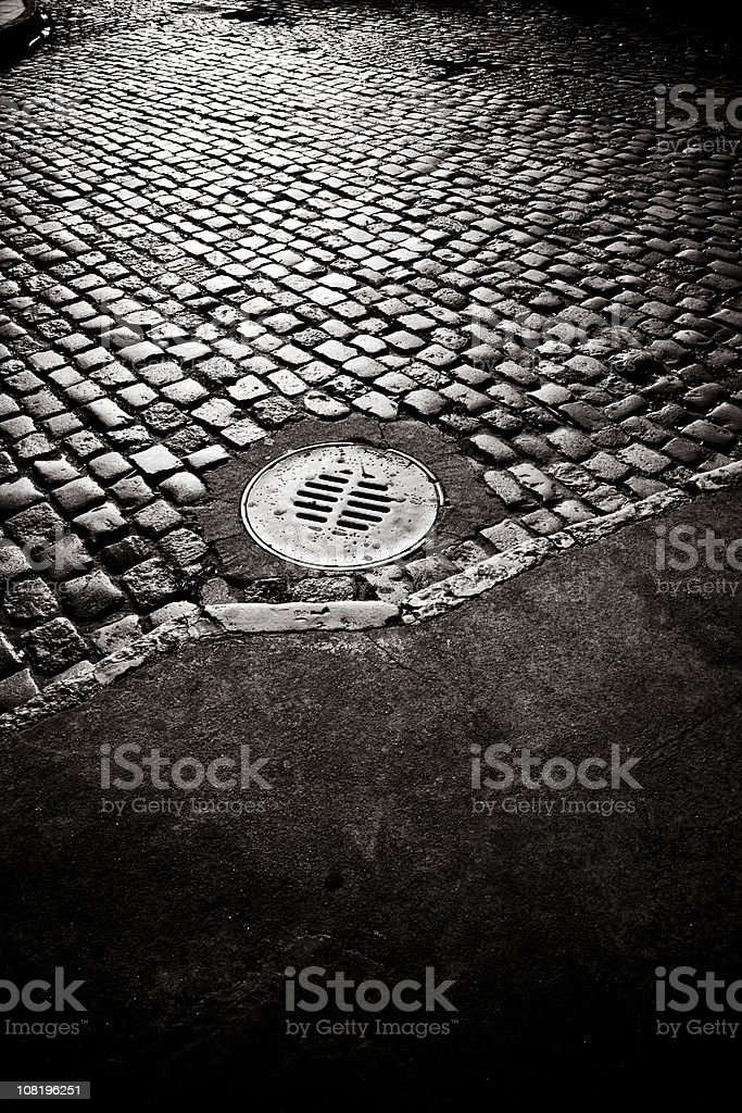 Old Cobble Stone Road with Sewer Cover, Black and White royalty-free stock photo