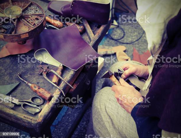 Old cobbler while repairing the shoe with a piece of leather with picture id926109906?b=1&k=6&m=926109906&s=612x612&h=r4bs1zpm115doxbcgnau0hn80tyxuibvhhxw0j6xgu8=