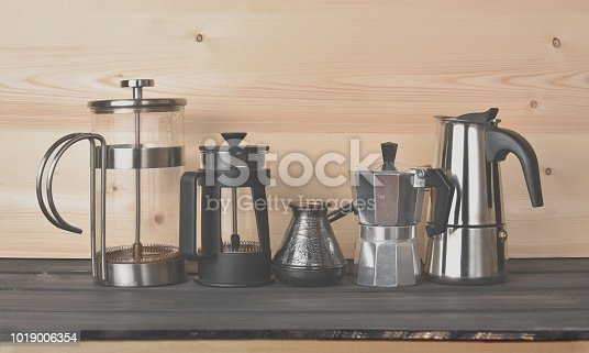 Old coffee makers on a wooden shelf. Vintage toned