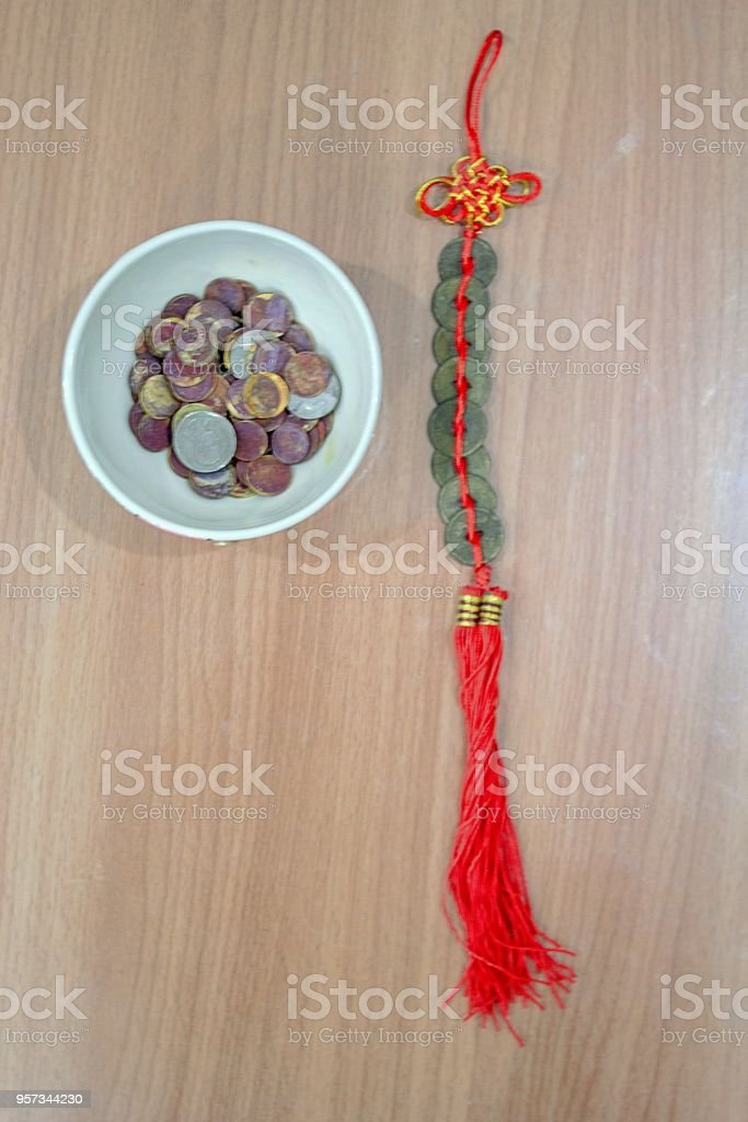 Old coins in a cup and a bunch of Chinese coins, roan, tie with red rope. stock photo