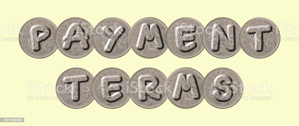 PAYMENT TERMS – Old coins on yellow background stock photo