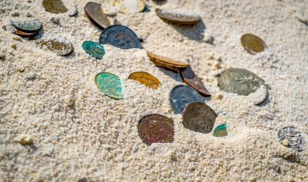 kısmen beyaz kuma gömülü eski paralar - gömülü stok fotoğraflar ve resimler