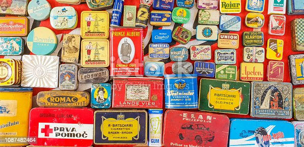 Old collection of tin boxes  on flea market sold together with other rustic objects outdoors along Ljubljanica river.