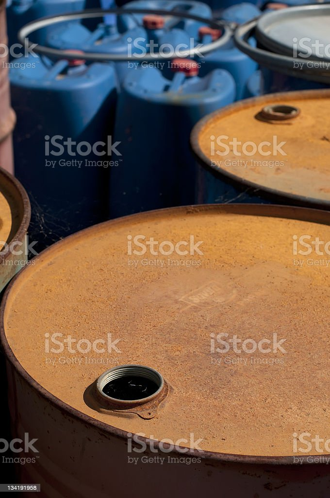 Old colored oil barrels and blue canisters royalty-free stock photo