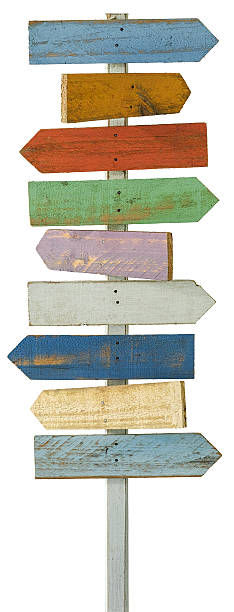 old colourful weathered wood arrow signboards pointing in opposite directions. - directional sign stock photos and pictures